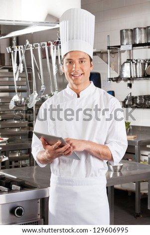 Portrait of young male chef with digital tablet in restaurant kitchen