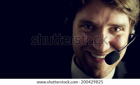 Portrait of young male customer service operator over black background, retro effect faded look. - stock photo