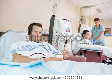 Portrait of young male dialysis patient holding glass of crushed ice during renal dialysis at hospital - stock photo