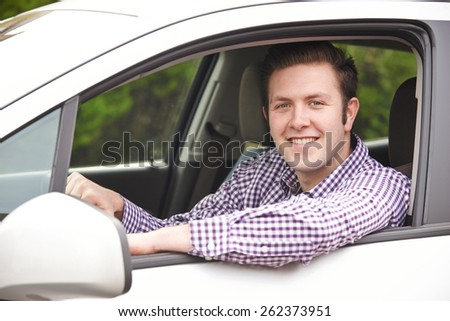 Portrait Of Young Male Driver Looking Out Of Car Window - stock photo