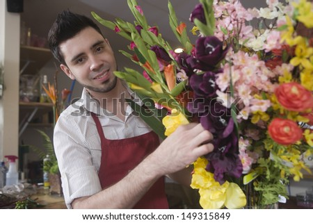 Portrait of young male florist decorating flower vase in shop - stock photo