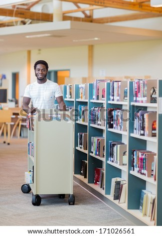Portrait of young male librarian with trolley of books in bookstore - stock photo