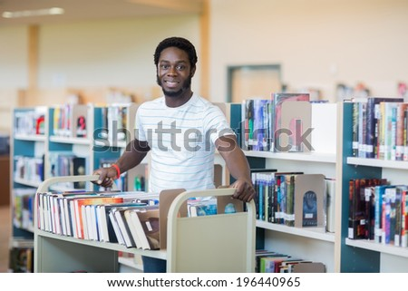 Portrait of young male librarian with trolley of books in library - stock photo
