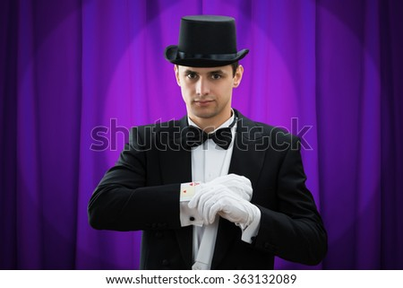 Portrait of young male magician performing magic trick with cards against purple curtain
