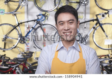 Portrait of young male mechanic in bicycle store - stock photo