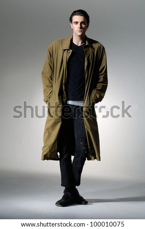 portrait of young male model in coat on light background