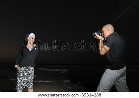 Portrait of young male photographer taking pictures of model at night