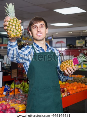Portrait of young male posing with ananas in grocery and smiling