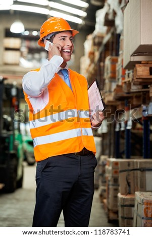 Portrait of young male supervisor using cell phone at warehouse - stock photo