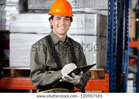 Portrait of young male supervisor with clipboard smiling at warehouse - stock photo