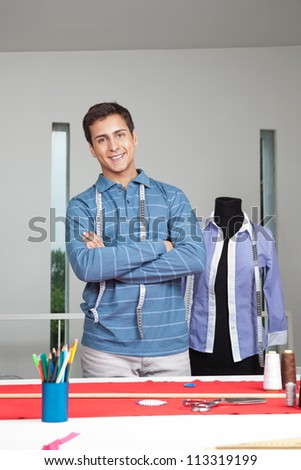 Portrait of young male tailor standing arms crossed with mannequin in background - stock photo