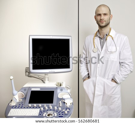 Portrait of young male technician operating ultrasound machine in white dress - stock photo
