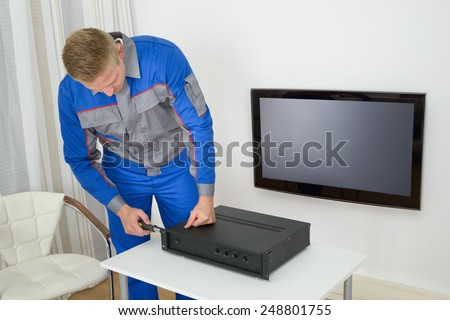 Portrait Of Young Male Technician Repairing Amplifier - stock photo
