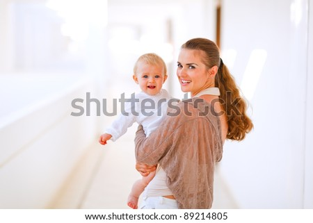 Portrait of young mama with adorable baby in hand - stock photo