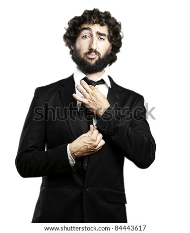 portrait of young man adjusting his suit against a white background - stock photo