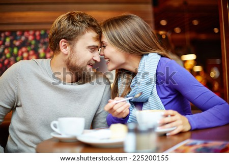 Portrait of young man and his girlfriend having date in cafe - stock photo