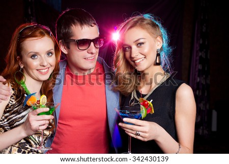 portrait of young man and two  girls on night party - stock photo