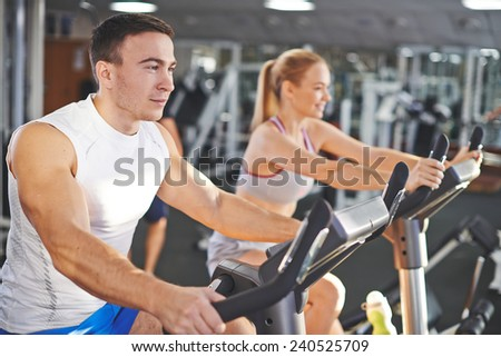 Portrait of young man and woman during workout in gym