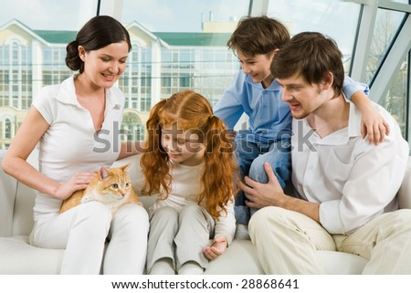 Portrait of young man and woman enjoying weekend day with their children and cute cat - stock photo