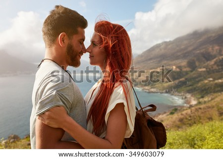 Portrait of young man and woman standing face to face. Affectionate young couple enjoying their love in nature outdoors. - stock photo