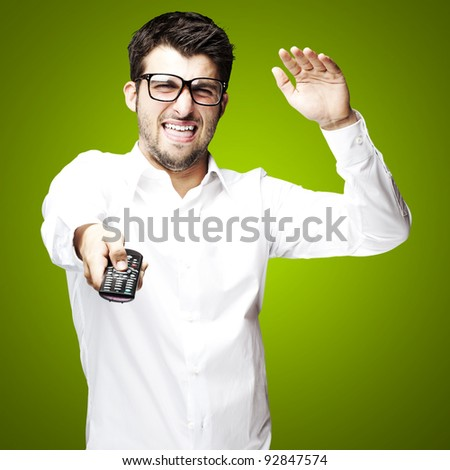 portrait of young man angry using tv control over green background - stock photo