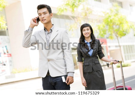 Portrait of young man asking how to find hotel on the phone - stock photo