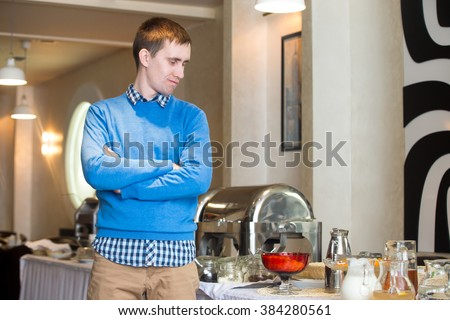 Portrait of young man at self-catering breakfast in hotel restaurant, picky eater fed-up with food, showing disappointment on his face - stock photo