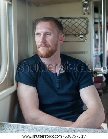 Portrait of   young man at  train window.
