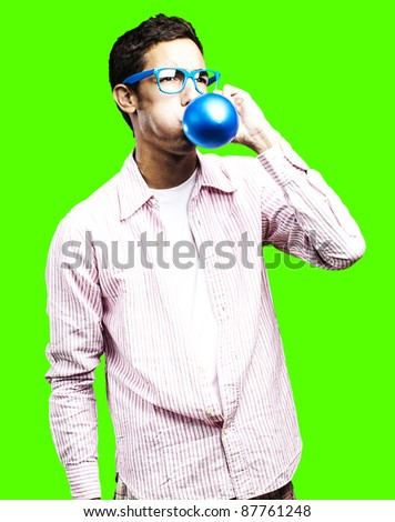 portrait of young man blowing a balloon against a removable chroma key background - stock photo