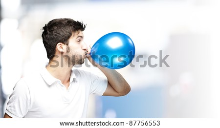 portrait of young man blowing a balloon indoor - stock photo