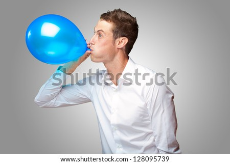 Portrait Of Young Man Blowing A Balloon Isolated On Grey Background