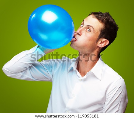 Portrait Of Young Man Blowing a� Balloon On Green Background - stock photo