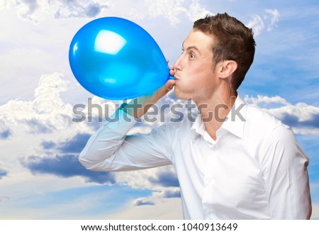 Portrait Of Young Man Blowing A Balloon, Outdoor