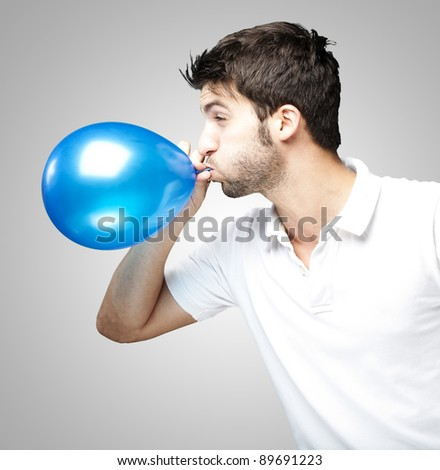 portrait of young man blowing a balloon over grey background - stock photo