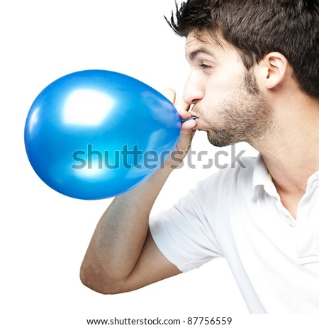 portrait of young man blowing a balloon over white background