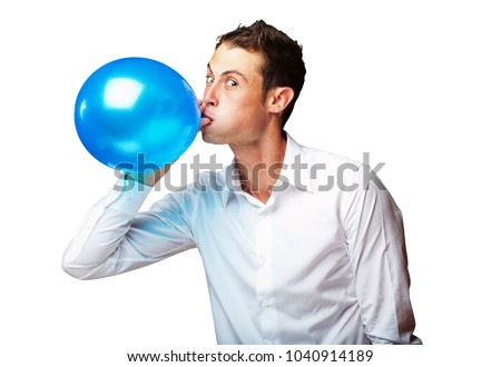 Portrait Of Young Man Blowing Balloon On White Background
