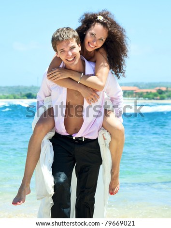 Portrait of young man carrying his cute young girlfriend on his back. The happy couple comes out of the ocean