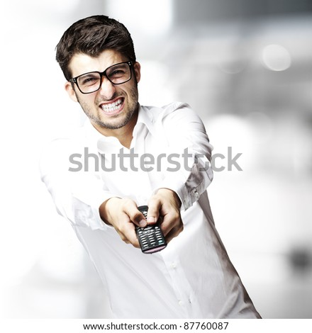 portrait of young man changing channel with tv control indoor - stock photo