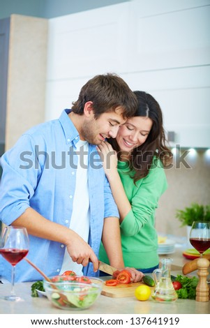 Portrait of young man cooking salad and his wife embracing him in the kitchen - stock photo