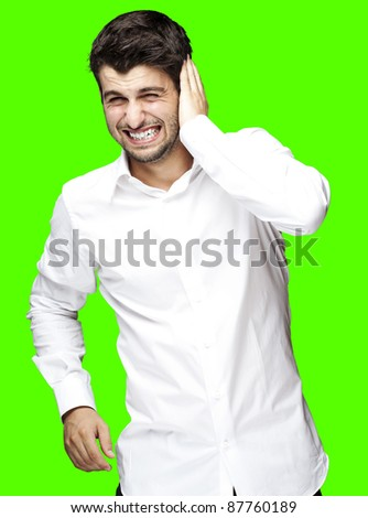 portrait of young man covering his ear against a removable chroma key background - stock photo