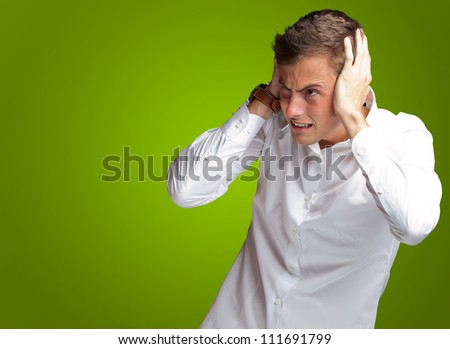 Portrait Of Young Man Covering His Ears With Hand On Green Background - stock photo
