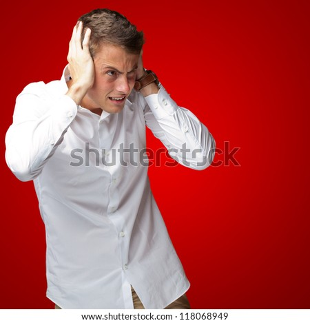Portrait Of Young Man Covering His Ears With Hand On Red Background - stock photo
