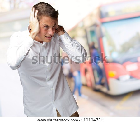 Portrait Of Young Man Covering His Ears With Hand, Outdoor - stock photo