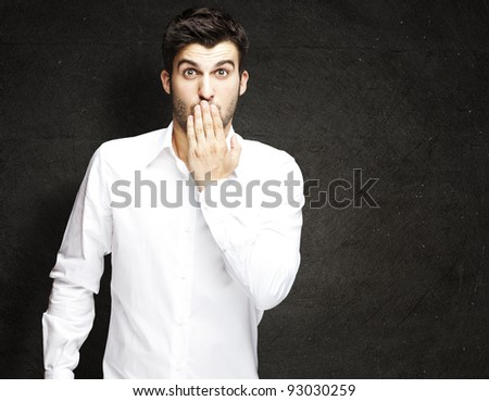 portrait of young man covering his mouth against a grunge wall - stock photo