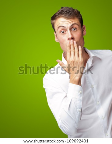 Portrait Of Young Man Covering His Mouth With Hand On Green Background - stock photo