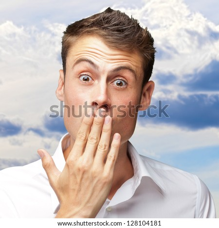 Portrait Of Young Man Covering His Mouth With Hand, Outdoor - stock photo