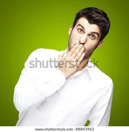 portrait of young man covering his mouth with hand over green - stock photo
