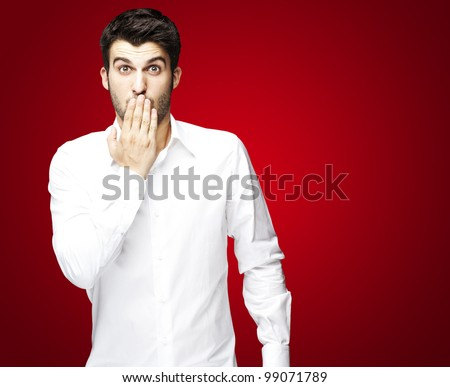portrait of young man covering his mouth with hand over red - stock photo