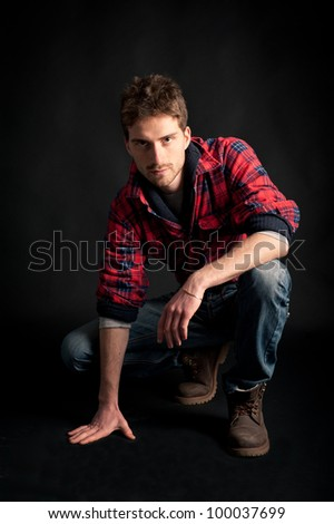 Portrait of young man crouched against black background. - stock photo