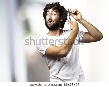 portrait of young man cutting himself hair indoor - stock photo